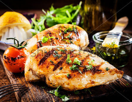 stock-photo-marinated-grilled-healthy-chicken-breasts-cooked-on-a-summer-bbq-and-served-with-fresh-herbs-and-184074431