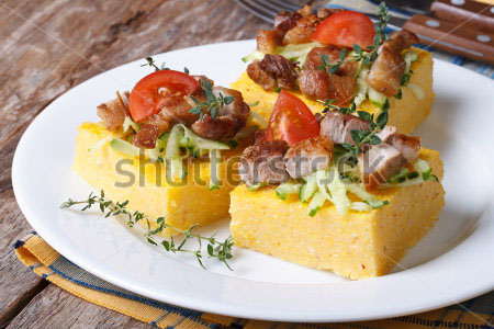 stock-photo-slices-of-tasty-polenta-with-meat-and-vegetables-on-a-white-plate-on-the-table-horizontal-203791810